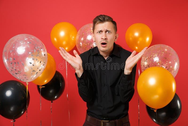 Zawodzący młody człowiek w czarnych klasycznych koszulowych podesłanie rękach na jaskrawego czerwonego tła lotniczych balonach St zdjęcie stock