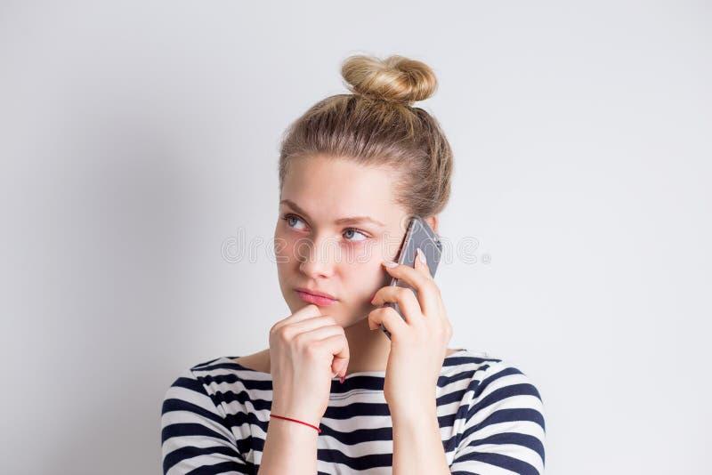Zawodzę udaremniał młodej biznesowej kobiety opowiada na smartphone nad białym tłem Niepomyślne negocjacje, zła wiadomość, fotografia royalty free
