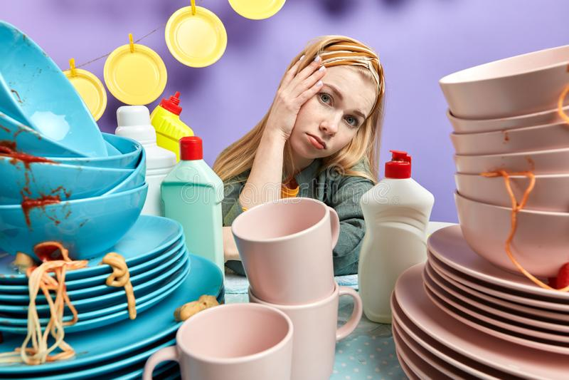 Zawodzący młody blondynki kobiety obsiadanie przy kicthen stołem zdjęcie royalty free