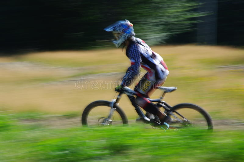 Zawoja, Poland - August 17, 2013. Downhill. Unknown cyclist riding fast on bicycle. stock photos