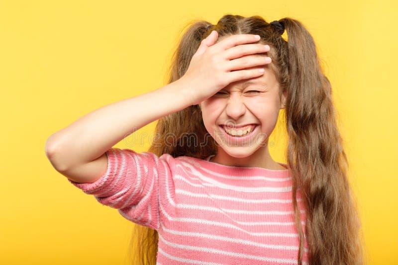 Zawstydzona uśmiechnięta dziewczyny pokrywy czoła ręka zawtydza obrazy stock