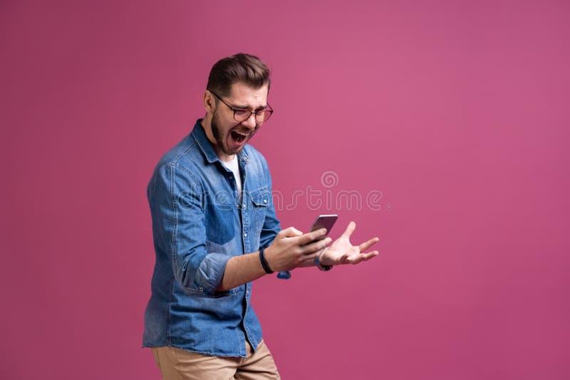 Zawsze w kontakcie Uśmiechnięty młody człowiek trzyma mądrze telefon i patrzeje je Portret szczęśliwy mężczyzna używa telefon kom zdjęcia royalty free
