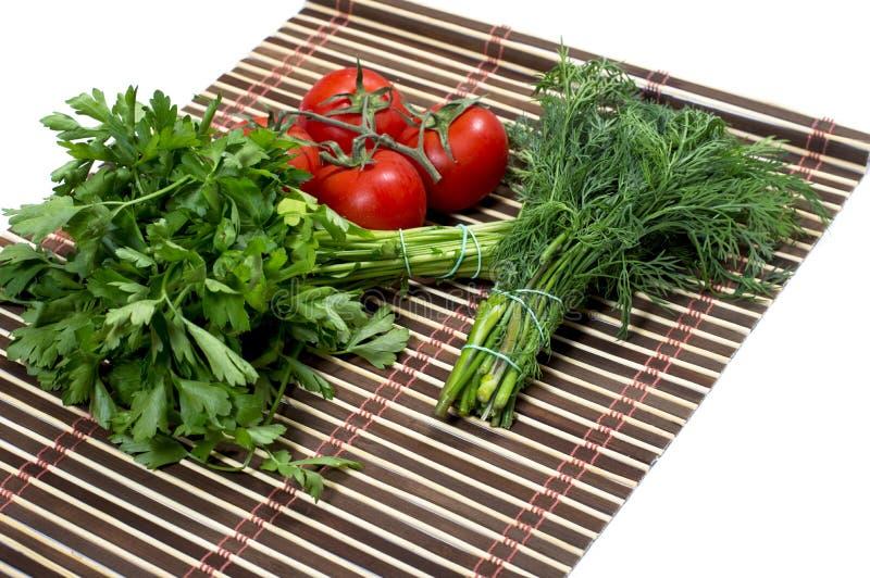 Zazębianie pietruszki, koperu i gałąź pomidor na dywaniku, zdjęcie royalty free