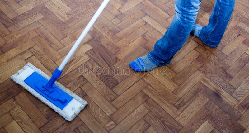 Zazzera che pulisce un pavimento di legno fotografia stock libera da diritti