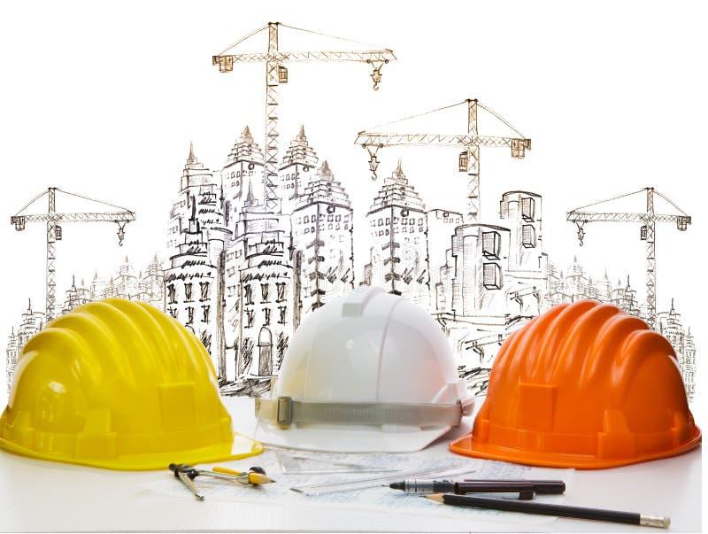 Zbawczy hełm na inżyniera pracującym stole przeciw kreślić budynek budowa i wysoki dźwigowy zbawczy hełm na inżyniera workin fotografia royalty free