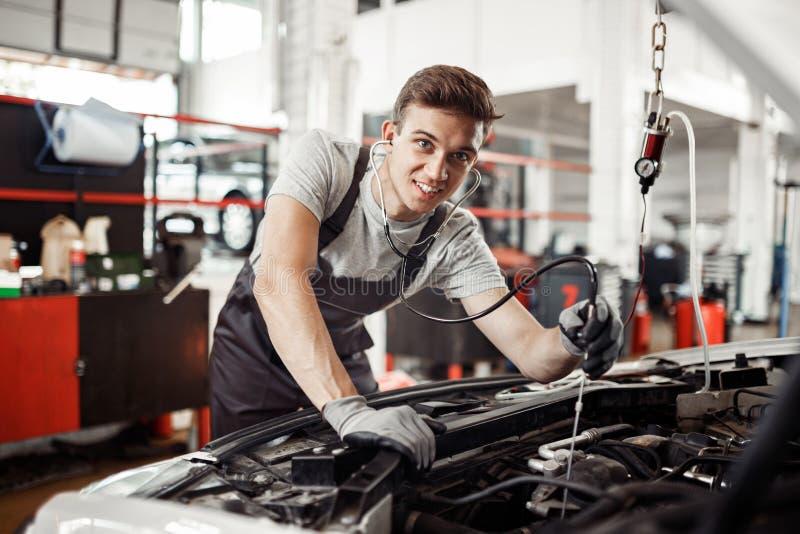 Zbawczy najpierw: młody ale dyplomowany automechanic prowadzi szczegółowego egzamin obraz royalty free