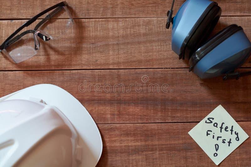 Zbawczy najpierw zauważa jeden żółtego kawałek papieru wtykającego na drewnianym tle z pełnym setem osobisty ochronny wyposażenie obrazy stock