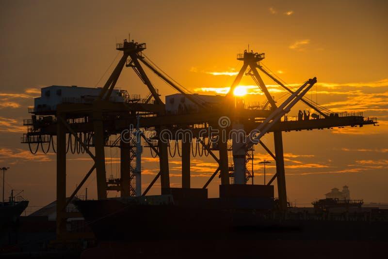 Zbiornika ładunku zafrachtowań statek z pracującym żurawia mostem w stoczni przy półmrokiem dla Logistycznie importa eksporta zdjęcia royalty free