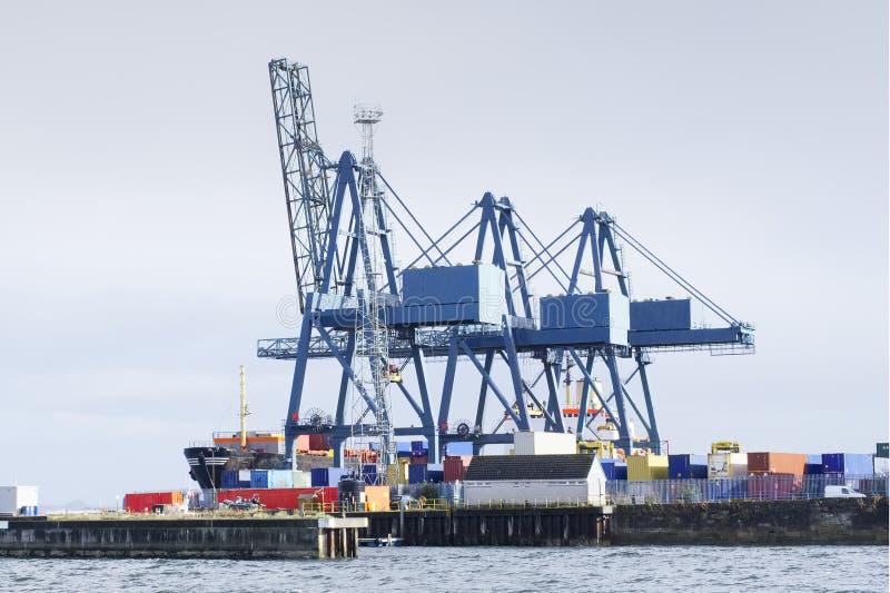 Zbiornika terminal dźwigowy kętnar dla ładować ładunek frachtową wysyłkę przy quay jarda schronienia dokiem na dennym wybrzeżu Gr zdjęcie stock