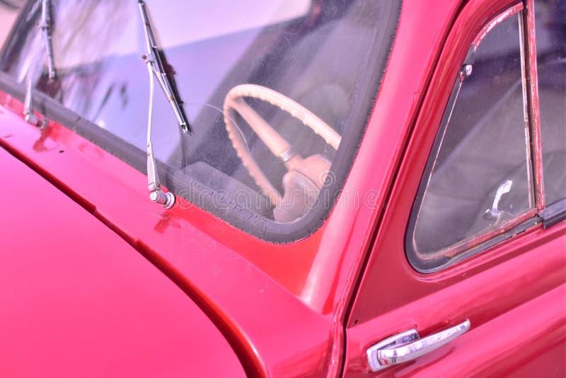 Zbliżenie frontowa strona retro czerwony samochód na miasto ulicie zdjęcia royalty free