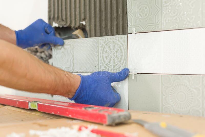 Zbliżenie kłaść ceramiczną płytkę na ścianie w kuchni kaflarz ręka, odświeżanie, naprawa, budowa fotografia royalty free