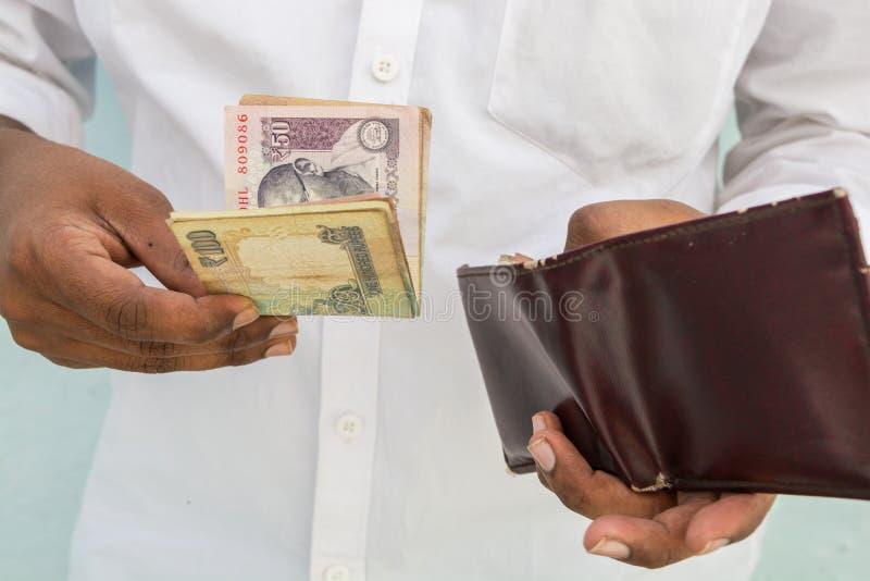 Zbliżenie mężczyzna wręcza brać Indiańską walutę z jego portfla fotografia stock