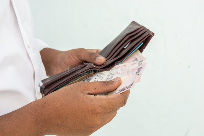 Zbliżenie mężczyzna wręcza brać Indiańską walutę z jego portfla obraz stock