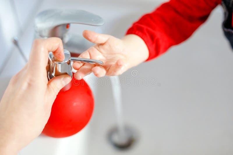 Zbliżenie małe berbeć dziewczyny domycia ręki z mydłem i wodą w łazience Matki lub ojca pomagać blisko do dziecka obrazy stock