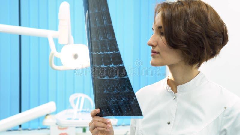 Zbliżenie portret intelektualna kobieta w białym labcoat, patrzeje pełnego ciała promieniowania rentgenowskiego radiograficznego  fotografia stock