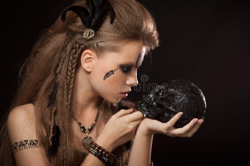 Zbliżenie portret szamańska kobieta z czarną ludzką czaszką obraz stock