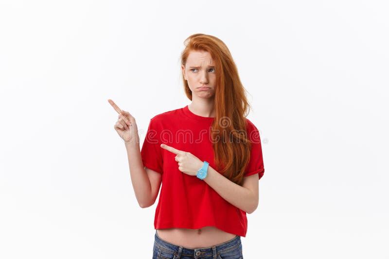 Zbliżenie poważna surowa młoda kobieta jest ubranym czerwonych koszulowych spojrzenia stresujących się i wskazują w górę palca od zdjęcia stock