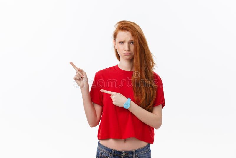 Zbliżenie poważna surowa młoda kobieta jest ubranym czerwonych koszulowych spojrzenia stresujących się i wskazują w górę palca od obrazy royalty free