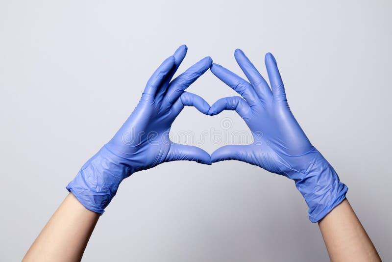 Zbliżenie ręka w lateksowych gumowych medycznych purpurowych rękawiczkach składał w serce znaka pojedynczy białe tło Pojęcie miło obraz royalty free