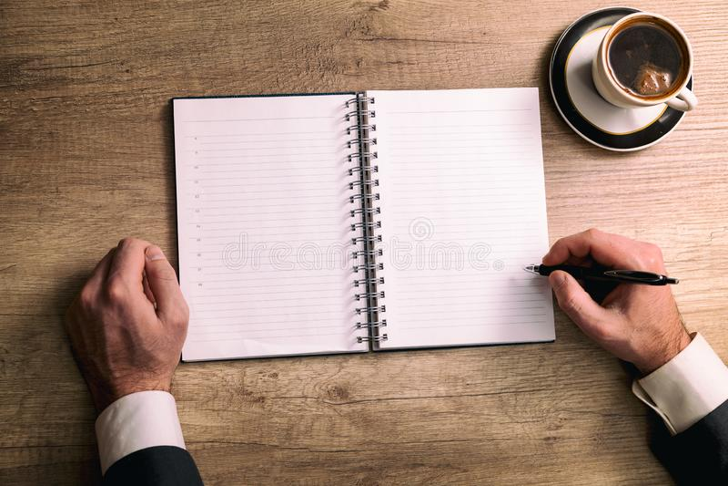 Zbliżenie strzał mężczyzna bierze puszek notatkę w osobistym organizatorze fotografia royalty free