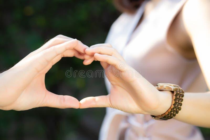 Zbliżenie szczęśliwa pary zabawa robi gestowi kierowemu kształtowi plenerowy z ręką wpólnie obraz royalty free