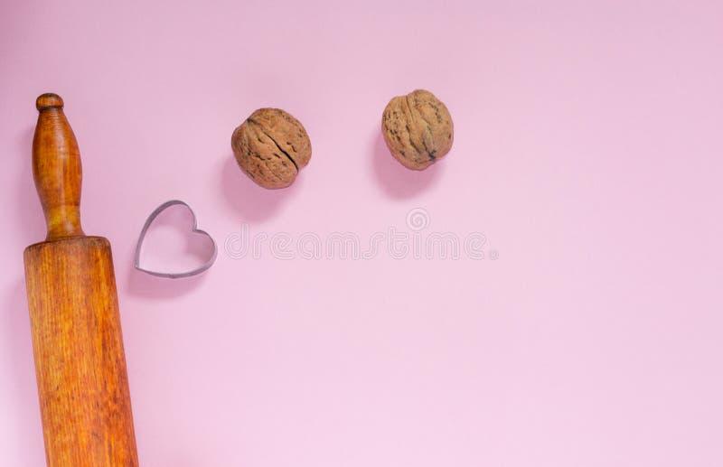 Zbliżenie tocznej szpilki metalu ciastka krajacz z kształtem serce i orzechy włoscy na różowym copyspace Kobiety miejsce pracy pr fotografia stock