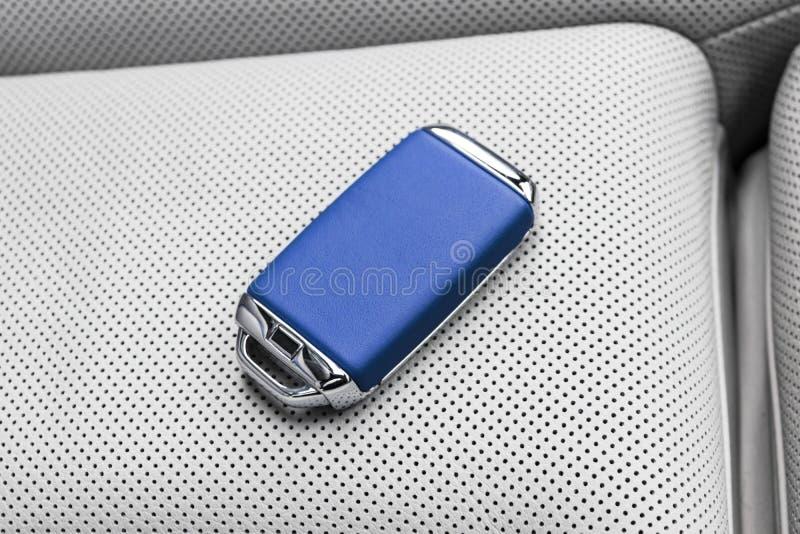 Zbliżenie wśrodku pojazdu bezprzewodowy błękitny skóra klucza zapłon na białej skóry siedzeniu Bezprzewodowy początku silnika klu zdjęcie royalty free