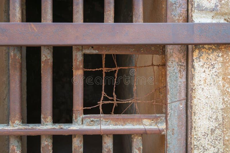 Zbliżenie zamknięci rdzewiejący stalowi pręt komórki drzwi w zamkniętym zaniechanym więzieniu zdjęcie royalty free