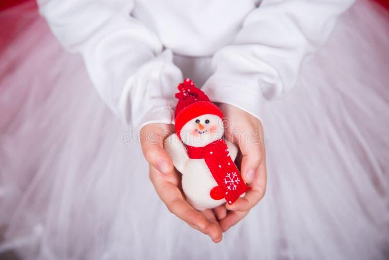 Zbliżeń dzieci ` s wręcza trzymać małego ładnego zabawkarskiego bałwanu w czerwonym kapeluszu i szaliku zdjęcie royalty free