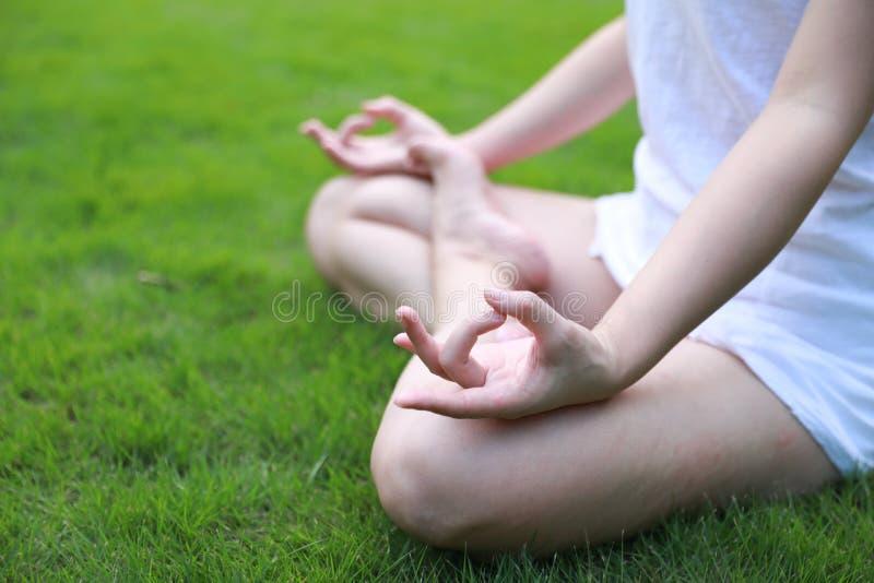Zbliżenia Azjatycki Chiński lying on the beach kłaść na trawa gazonu główkowaniu robi joga pozie w lasu parka światła słonecznego fotografia royalty free