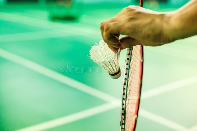 Zbliżenia Badminton gracza ręka trzyma wahadłowa koguta wraz z kantem, przygotowywającym słuzyć pozycję na sztuki zieleni sądzie  obraz stock