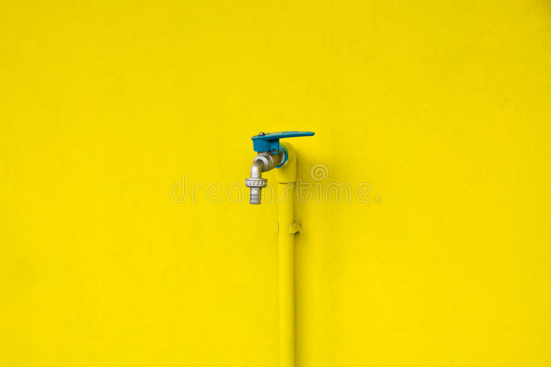Zbliżenia faucet na betonowym kolor żółty ściany tle Wodny wyciek obrazy royalty free