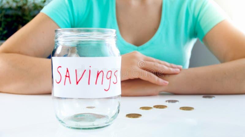 Zbliżenia iamge młoda kobieta i pusty szklany słój dla pieniędzy savings zdjęcie stock