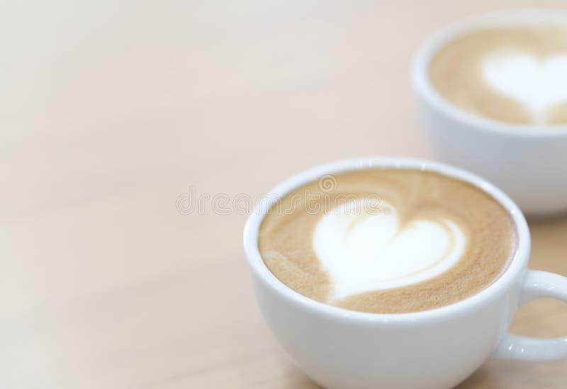 Zbliżenia latte sztuki kawa z kierowym kształtem w białej filiżance dla relaksuje zdjęcia stock