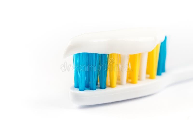Zbliżenia makro- pasta do zębów na toothbrush odizolowywającym nad białym tłem obraz stock