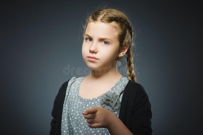 Zbliżenia Rozważny lub pogardliwy dziewczyny przedstawienie przy kamerą odizolowywającą na szarość zdjęcie stock