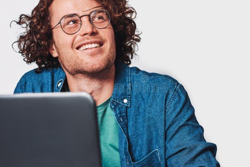 Zbliżenia studia strzał młody uśmiechnięty mężczyzna z kędzierzawego włosy obsiadaniem przy stołowym działaniem przy laptopem i m obraz royalty free