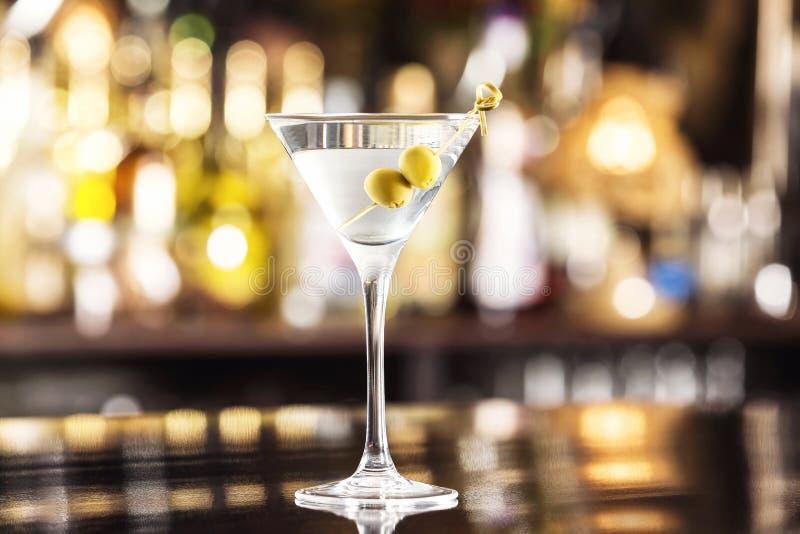 Zbliżenia szkło Martini suchy koktajl z oliwkami przy baru kontuarem obrazy stock