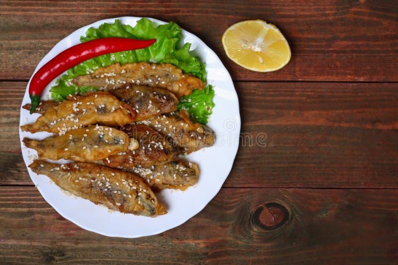 Zbliżenia talerz z hiszpańskimi boquerones fritos, obijać i smażyć sardelami typowymi w Hiszpania, na nieociosanym drewnianym sto obrazy royalty free