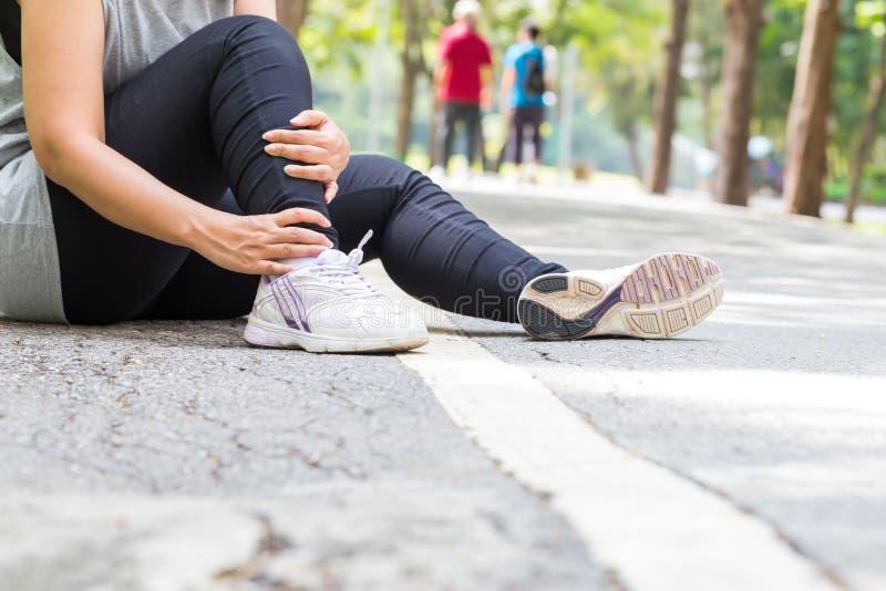 zbliżenia urazu nogi mięśnia bólu biegacza działający sporty plamią uda macanie Kobieta z bólem w kostce podczas gdy jogging obraz stock