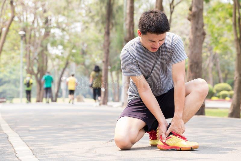 zbliżenia urazu nogi mięśnia bólu biegacza działający sporty plamią uda macanie Mężczyzna z bólem w kostce podczas gdy jogging zdjęcia stock