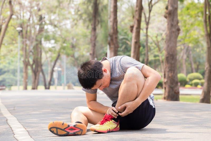 zbliżenia urazu nogi mięśnia bólu biegacza działający sporty plamią uda macanie Mężczyzna z bólem w kostce podczas gdy jogging zdjęcie stock