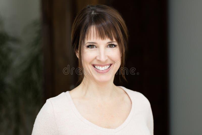 Zbliżenie Ładna kobieta ono Uśmiecha się Przy kamerą W Domu fotografia royalty free
