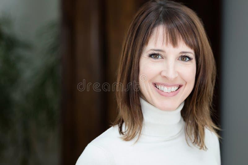 Zbliżenie Ładna kobieta ono Uśmiecha się Przy kamerą W Domu zdjęcia royalty free