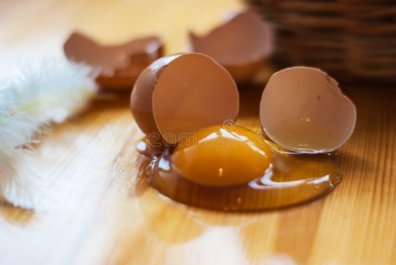 Zbliżenie łamany jajko i piórko na kuchennym stole, koszykowy d obrazy royalty free