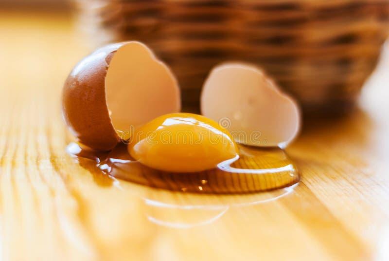 Zbliżenie łamany jajko na kuchennym stole, koszykowi defocuses Gr fotografia royalty free