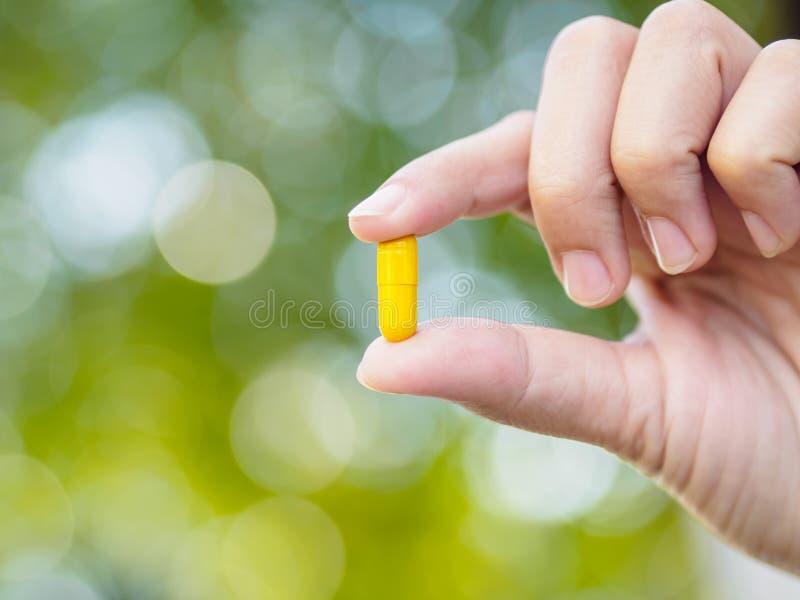 Zbliżenie żółte pigułki w kobiety ręce z bokeh tłem zdjęcie royalty free