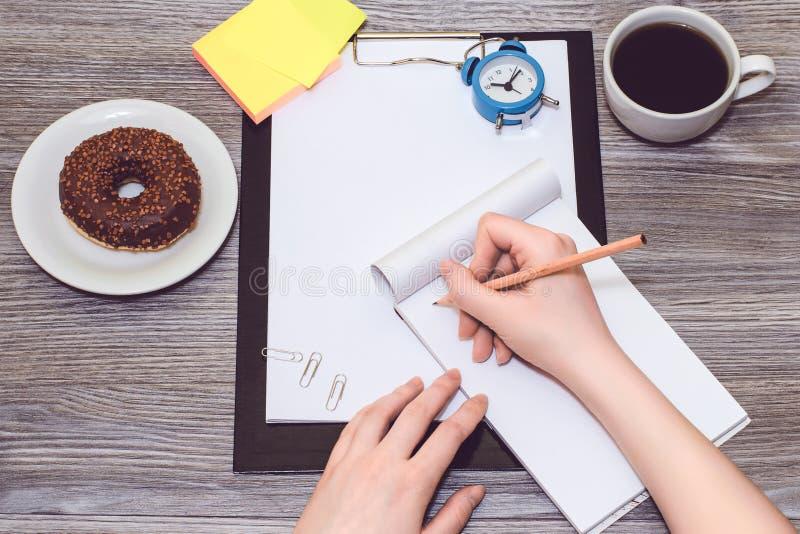 Zbliżenie żeński ` s wręcza writing z ołówkiem w notepad obrazy stock