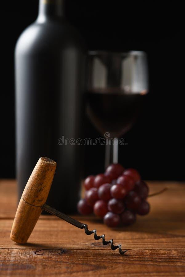 Zbliżenie antykwarska korek śruba z z ostrości czerwonego wina butelką, winogronami i wineglass w tle, obrazy stock