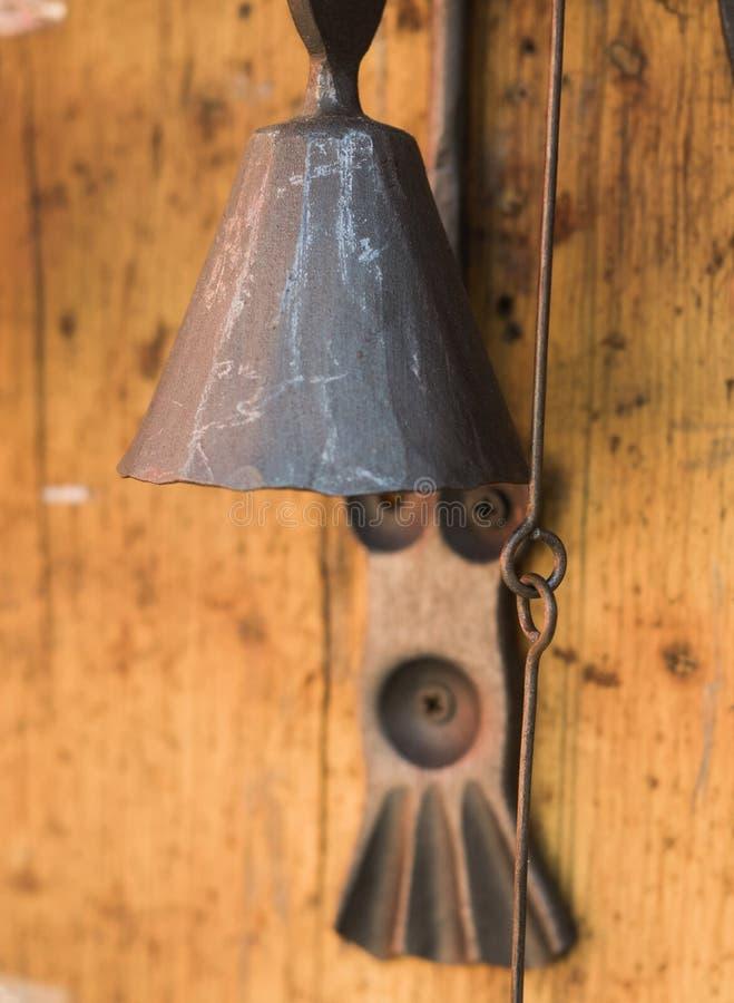Zbliżenie antykwarski ośniedziały dzwon na stiuk ścianie zdjęcia royalty free